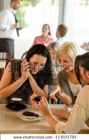 Friends looking at photographs and laughing cafe woman fun enjoying - stock photo