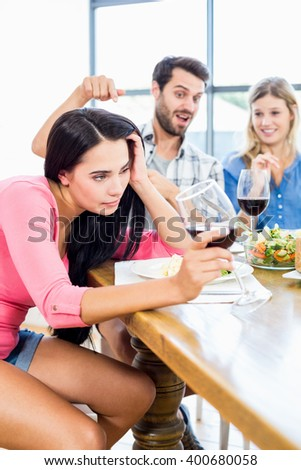 Friends looking drunk woman with wine glass at home - stock photo