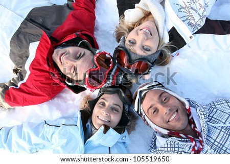 Friends lying in the snow - stock photo