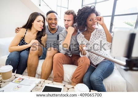 Friends making funny faces while taking a selfie in living room - stock photo