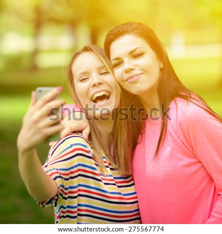Friends making selfie on beautiful summer day in park - stock photo