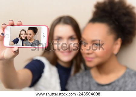 Friends making selfie. Selective focus image of  two beautiful young women making selfie and grimacing while sitting in the restaurant - stock photo