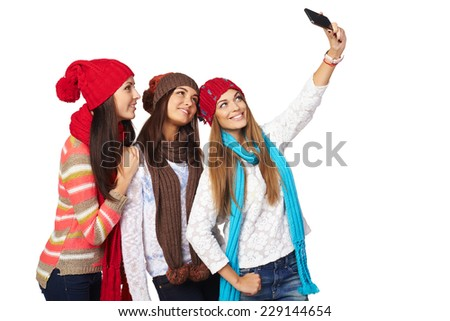 Friends making selfie. Three beautiful young women wearing warm winter clothing making selfie - stock photo