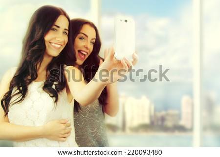 Friends making selfie. Two beautiful young women making selfie   - stock photo