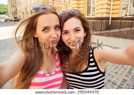 Friends making selfie. Two beautiful young women making  selfie and smiling - stock photo