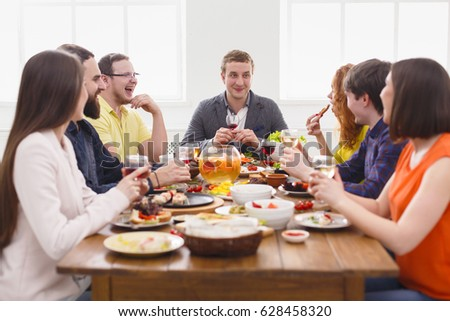 Friends meeting. Group of happy people talking, eating healthy meals at party dinner table in cafe, restaurant. Young company celebrate with alcohol and food at wooden table indoors.