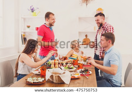 Friends meeting. Group of happy people with glasses saying toast, cheers, talking, laughing at party dinner table in cafe, restaurant. Young company celebrate with alcohol and food at wooden table