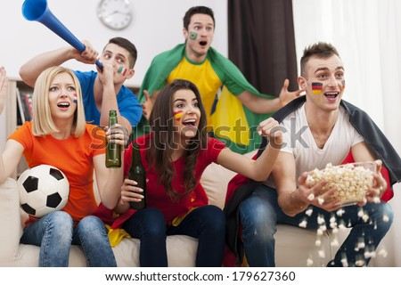 Friends of different nations supporting football team   - stock photo