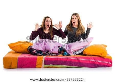 Friends on bed doing surprise gesture - stock photo