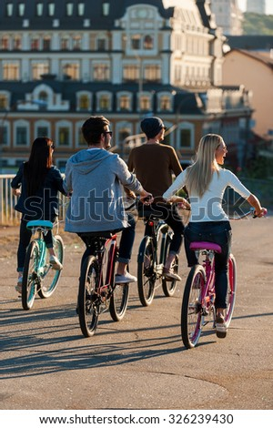 Friends on bicycles. Rear view of four young people riding down the street together - stock photo