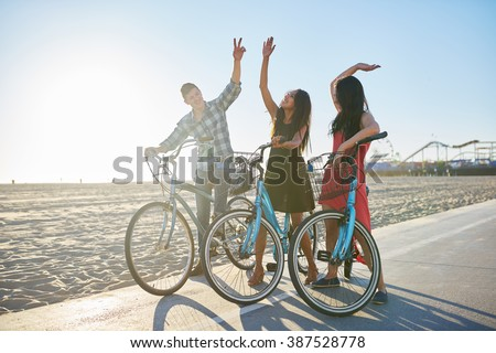 friends on bike doing high five together - stock photo