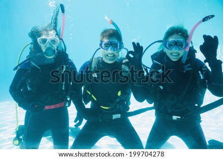Friends on scuba training submerged in swimming pool making ok sign on their holidays - stock photo