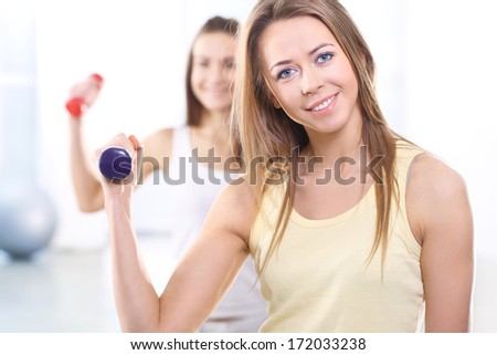 Friends on treningy forcefield  / Beautiful, young, slim, athletic woman during a workout at the gym - stock photo