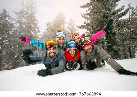 friends on winter holidays â?? Happy skiers lying on snow and having fun