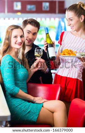 Friends or couple eating fast food in American fast food diner, the waitress serving the food and wine