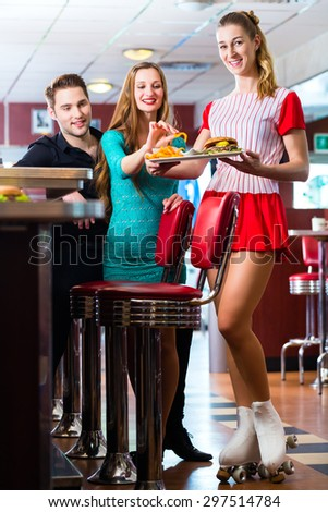 Friends or couple eating fast food in American fast food diner, the waitress wearing a short costume and roller skates - stock photo