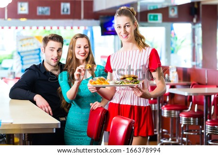 Friends or couple eating fast food in American fast food diner, the waitress wearing a short costume - stock photo