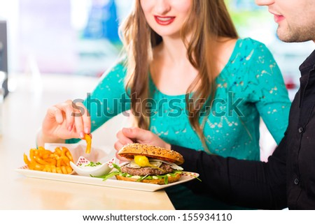 Friends or couple eating fast food with burger and fries in American fast food diner - stock photo