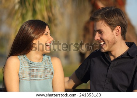 Friends or couple laughing and taking a conversation sitting on a bench in a park - stock photo