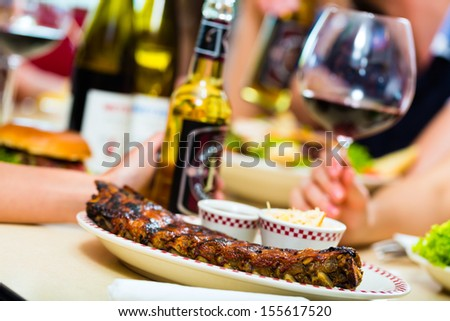Friends or couples eating fast food and drinking beer and wine in a American fast food diner - stock photo