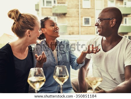 Friends out dining, multi ethnic concept, laughing and having a good time - stock photo