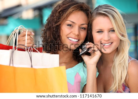 Friends out shopping with a cellphone - stock photo