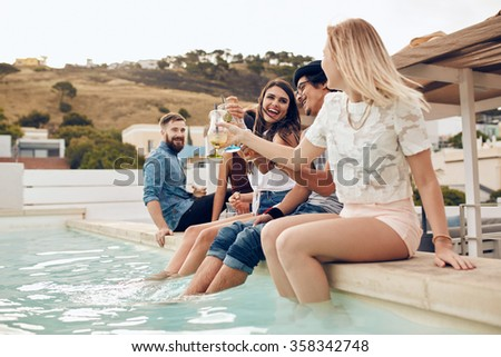 Friends partying outdoor sitting by the pool and toasting drinks. Group of young people having party by a swimming pool. Man and woman relaxing by a pool with their feet in water. - stock photo
