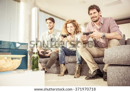 Friends playing in the living room and having fun . Straight focus on the faces. concept about home entertainment - stock photo