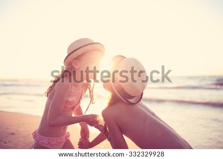Friends playing on beach on the sunny end of a day - stock photo