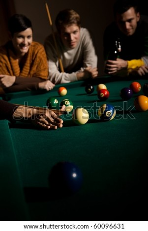 Friends playing snooker, female hand with cue in focus, aiming at ball.? - stock photo