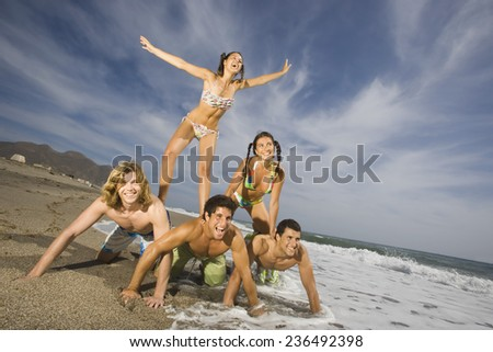 Friends Playing Together on Beach - stock photo