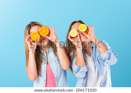 Friends playing with fruits over blue background - stock photo