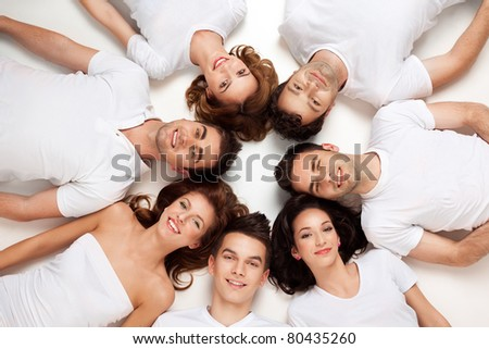 friends posing laying down on the floor looking at camera - stock photo