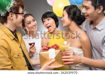 Friends presenting a gift to a girl