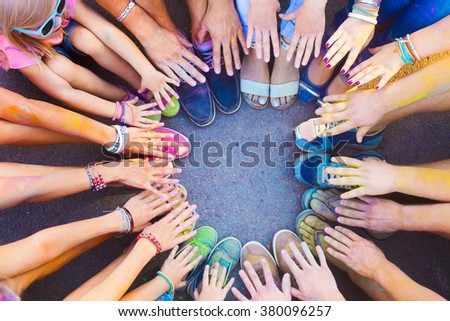 Friends putting their feet and hands together in a sign of unity and teamwork. Holi colors festival. Friendship concept