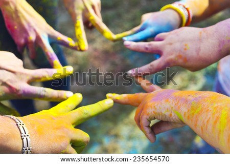 Friends putting their hands together in a sign of unity and teamwork. Holi colors festival. Friendship concept - stock photo