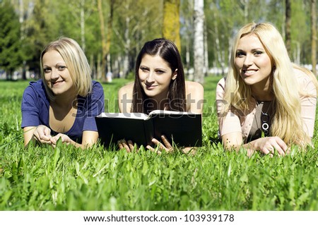 friends read the book on the nature - stock photo