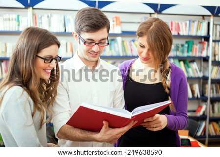 Friends reading a book in a library - stock photo