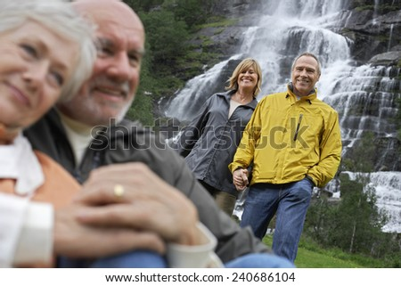 Friends Relaxing by Waterfall