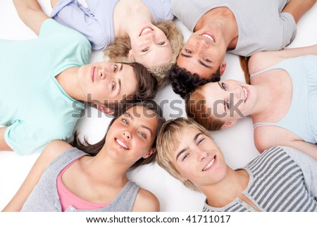 Friends relaxing on floor with heads together in a circle - stock photo