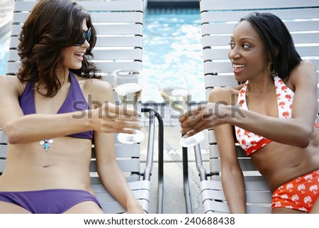 Friends Relaxing with White Wine by Swimming Pool - stock photo