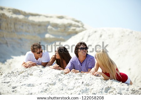 Friends resting on the sand and chatting with each other - stock photo