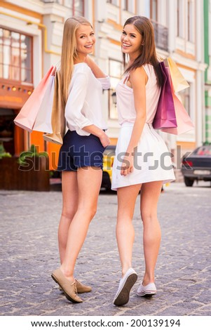 Friends shopping. Rear view of two beautiful young women holding shopping bags and looking over shoulder with smile while standing outdoors - stock photo