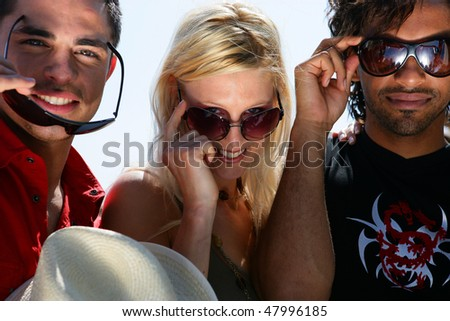Friends showing off with sunglasses on - stock photo