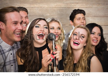 Friends singing karaoke against wooden surface with planks - stock photo