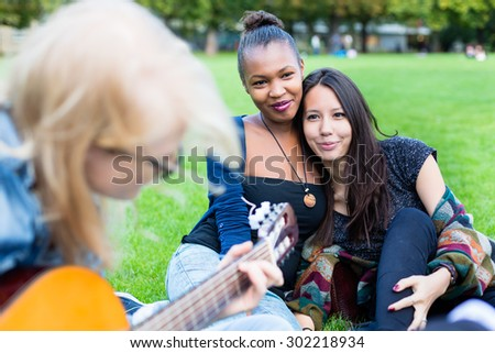 Friends singing songs in park having fun together with one girl playing the guitar, diversity group of African, Asian and Caucasian people