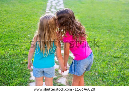 friends sister girls whispering secret in ear in grass garden track park outdoor - stock photo