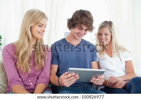Friends sit together on the couch as they all look at a tablet pc