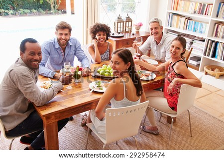 Friends sitting at a dining table looking at the camera - stock photo