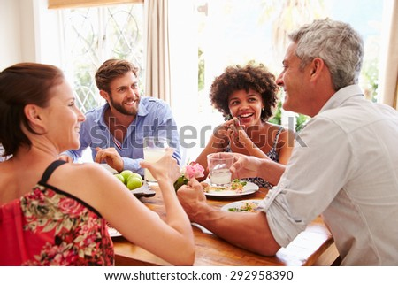 Friends sitting at a table talking during a dinner party - stock photo